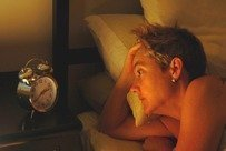 sleepless woman looks at alarm clock (from Stress Express book)